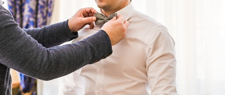 dinner wear: Fashion photo of a man with beard correcting his bowtie