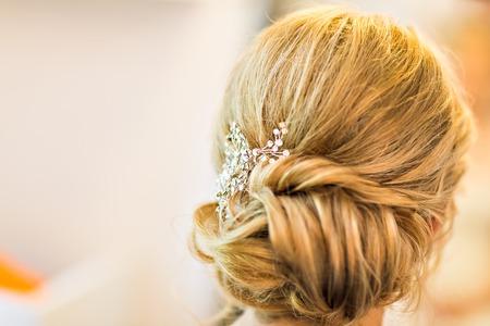 Estilista de pelo hace que la novia antes de la boda