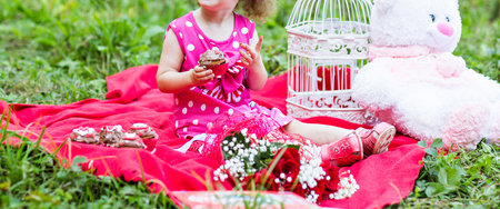 picnicking: Family  picnicking together. little girl holding a cake