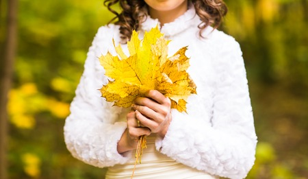 image created 21st century: Woman holding a bouquet of maple leaves Stock Photo