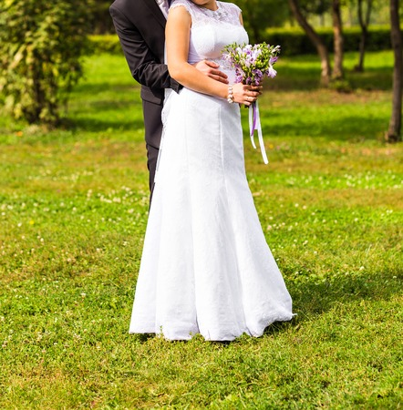 embraced: Just married couple embraced in a park Stock Photo