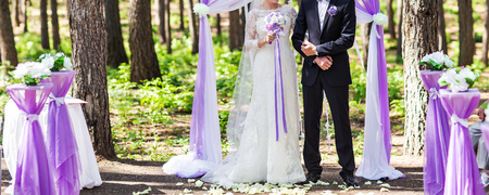 getting married: Couple Getting Married at an Outdoor Wedding Ceremony Stock Photo