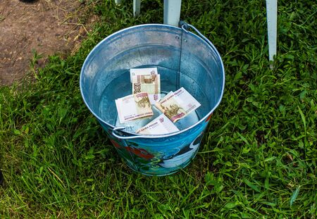 bucket of money: Money Russian banknotes in a bucket of water Stock Photo