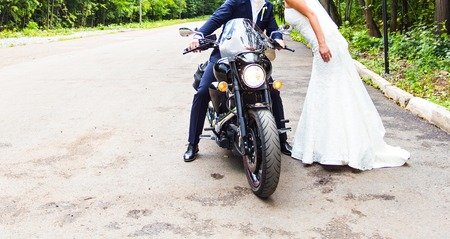 Happy wedding couple having fun on motorcycle