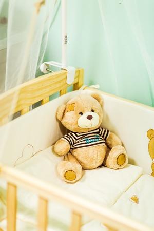 Teddy Bear toy alone in the crib