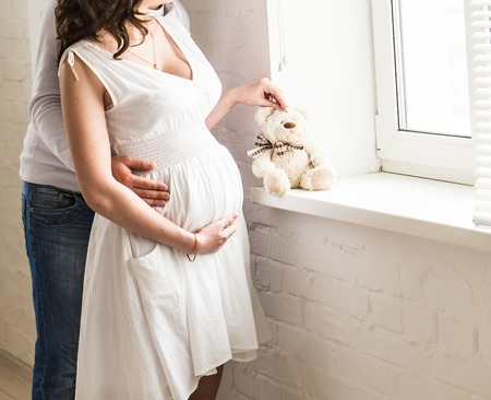 Beautiful pregnant woman with her husband in the room