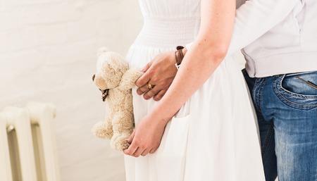 Hermosa mujer embarazada con su marido en la habitación