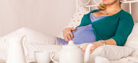 expectant arms: Pregnant woman relaxing at home on the bed