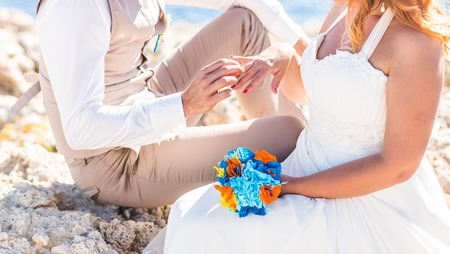 fingers put together: Man putting on golden ring on a womans finger, sea background