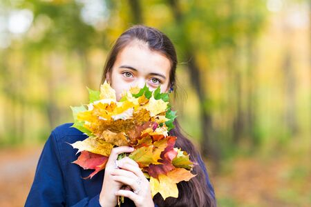 covering the face: Young woman covering face with an autumn leaf