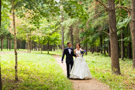 bride dress: happy bride and groom at a park on their wedding day Stock Photo