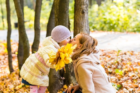in kiss: Mother kissing her daughter in the park. Woman kissing her baby girl. Woman with child outdoor in summer park. Happy family playing outdoor Stock Photo