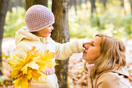 fall of the leaves: happy mother and  little daughter playing on autumn walk