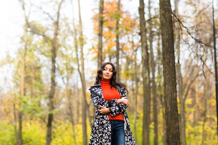 dispassionate: Portrait of young serious  woman standing at autumn park. Stock Photo