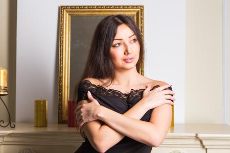 mujer sexy: belleza yong morena mujer sentada cerca de la chimenea en casa Foto de archivo