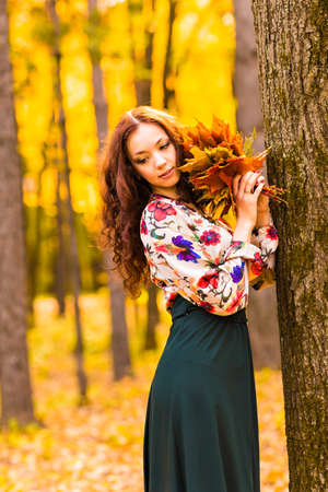 woman standing: Beautiful elegant woman standing in a park in autumn Stock Photo
