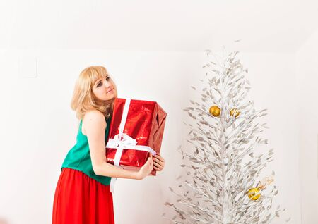 christmas present box: Happy young woman opening present box near a christmas tree Stock Photo