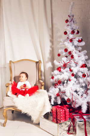 sits on a chair: a little girl sits in a chair near the Christmas tree