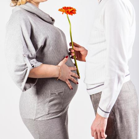 marido y mujer: La mujer embarazada y su marido aislados en blanco. Marido da una flor a su esposa embarazada