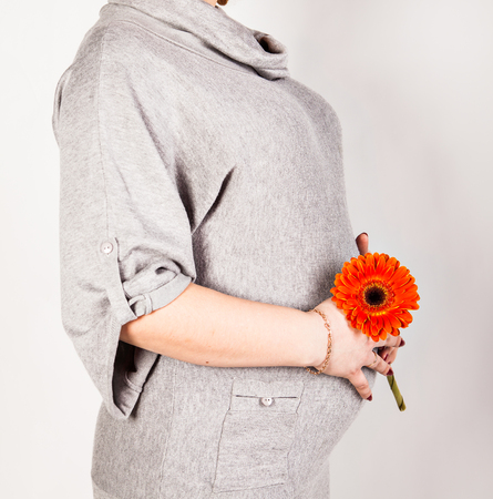 fruition: Pregnant woman holding her belly and orange flower