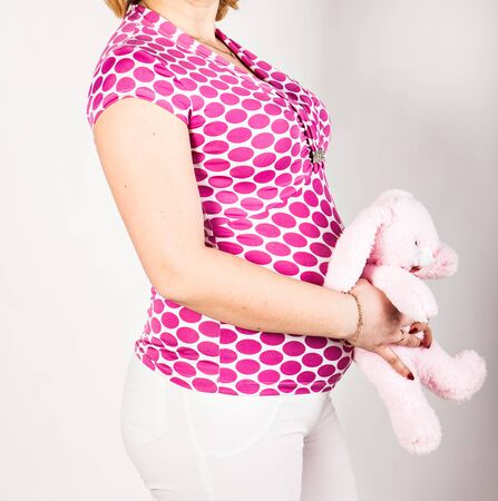 beautiful womb: Young pregnant woman with  toy on her belly Stock Photo