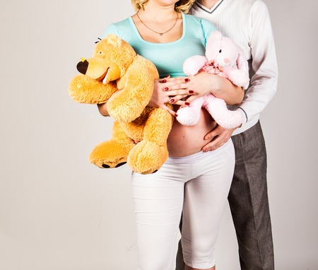 beautiful womb: Young pregnant woman with husband and toy