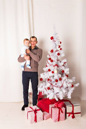 baby near christmas tree: Father with a baby near Christmas tree. Concept of happy childhood. Celebrating Christmas in a homely atmosphere. Father dabbles with the child, laughing merrily.Merry Christmas. Family celebration.