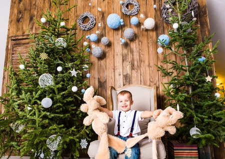 giftware: Boy  sitting in  chair near Christmas tree and gifts