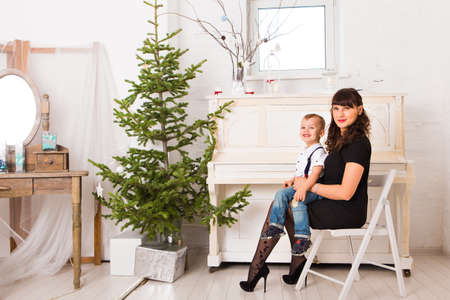 christmas tree decoration: Happy mother and  her son playing near an decorated fir-tree for Christmas
