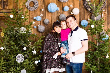 jovenes felices: Retrato de la familia amistoso mirando la c�mara en la noche de Navidad Foto de archivo