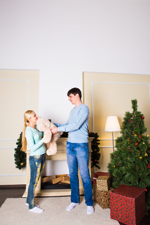 young tree: Christmas Gift. Happy Couple with Christmas and New Year Gift at Home. Smiling Family