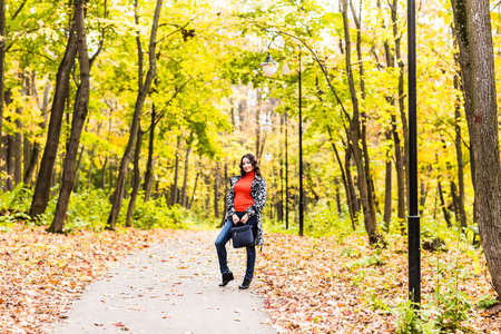 street wise: Beautiful young woman walking  in autumn park