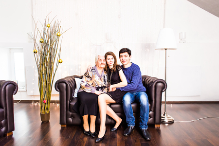 6 9 years: Portrait of a happy family with grandmother smiling at home in living room