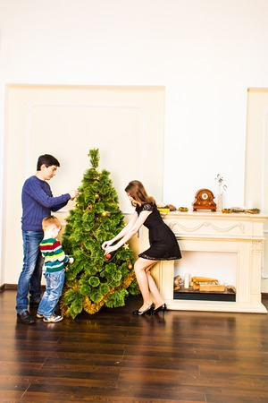 children love: Family decorating a Christmas tree with boubles in the living-room. Stock Photo