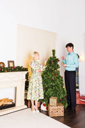 taking a wife: Happy Couple Decorating Christmas Tree in their Home. Smiling Man and Woman together Celebrating Christmas or New Year. Christmas Tree Decoration.Family