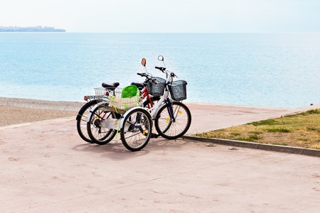 attached: Two attached bicycles near the coast, during holidays