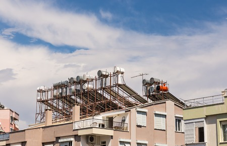 solar panels with water collector on the roof of house. Imagens