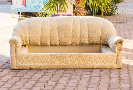 dumped: Old abandoned beige   couch dumped on the street