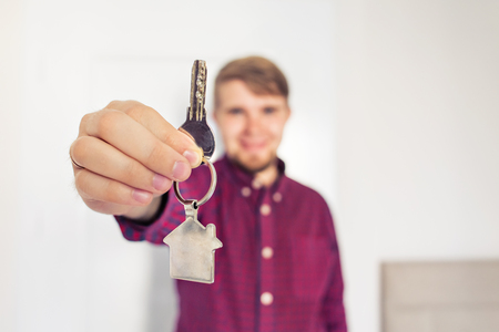 housewarming: Holding out house keys. Housewarming. man holds the keys of the house
