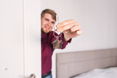 renter: Holding out house keys. Housewarming. man holds the keys of the house