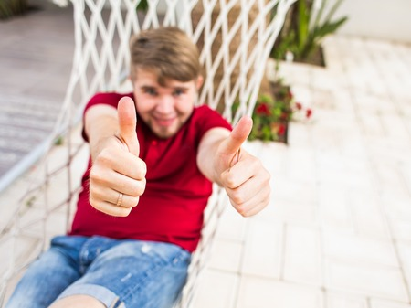 settle back: Man Relaxing In Hammock and shows thumb up