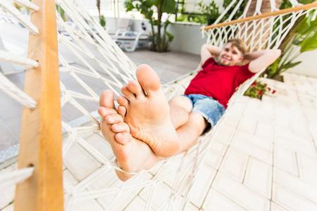 settle back: Man Relaxing In Hammock near the pool Stock Photo