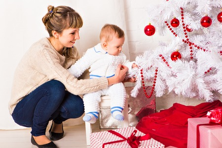 baby near christmas tree: Portrait of smiling young mother with beautiful baby  near Christmas tree Stock Photo
