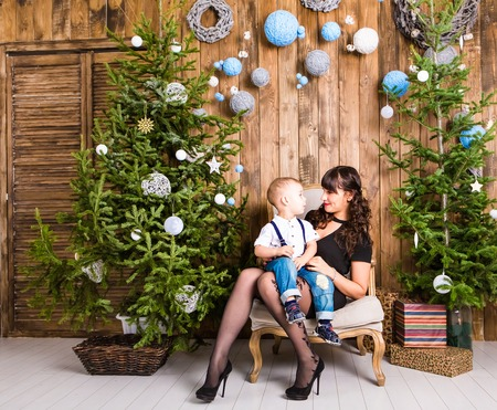 baby near christmas tree: Portrait of happy mother and baby near a christmas tree.