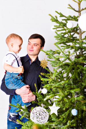 decorate: Happy father and son decorate Christmas tree.