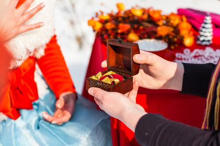 proposing: love, couple, christmas, x-mas, winter, relationship and dating concept - romantic man proposing to a woman. Stock Photo