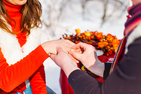 proposing: man putting wedding ring on woman hand. Christmas and New Year decoration - tree, gifts and wedding bouquet