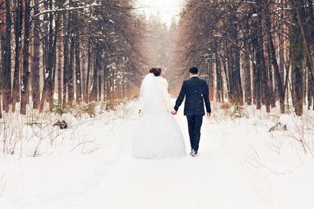 svatba: Nevěsta a ženich v zimním lese.