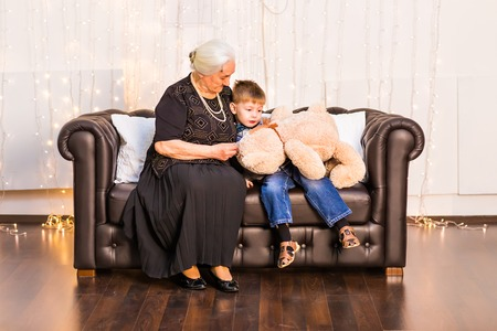 boy lady: Lovely little boy with his grandmother having fun and happy moments together at home