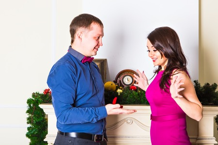 will you marry me: Will you marry me. Handsome young man making a proposal while giving an engagement ring to his girlfriend with Christmas Decoration in the background.